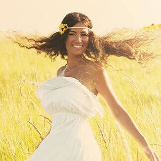 A woman wearing a floral wreath and sleeveless white dress spinning around in field of grass.