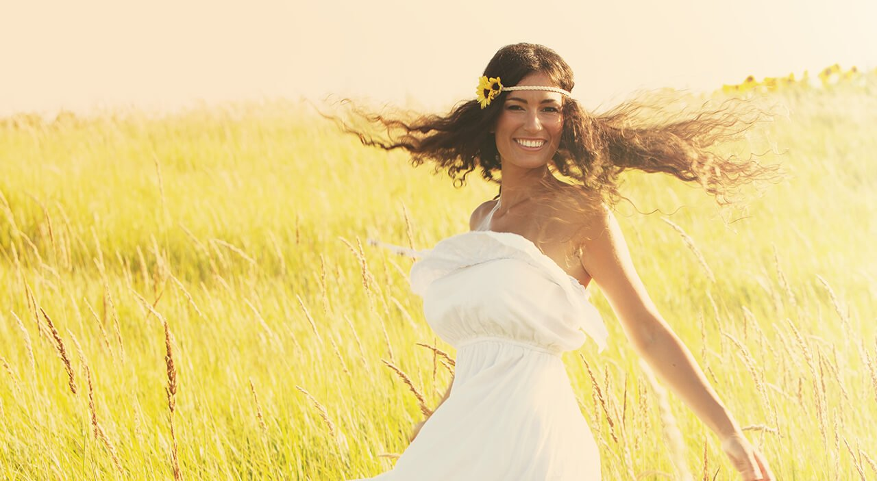 Woman with long brown hair smiling wearing strapless dress and dancing in a grassy field.