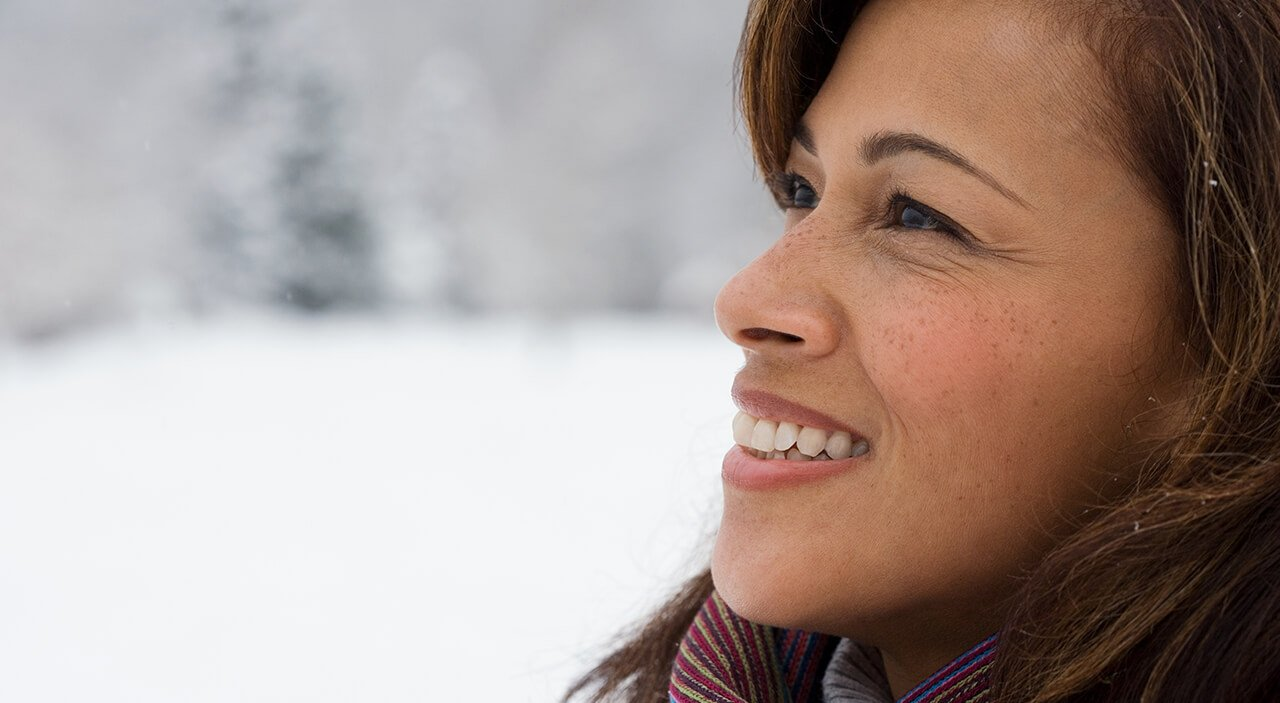 Older woman with brown hair looking upward and smiling  against snowy background.