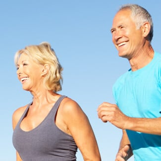 Older woman and man jogging on the beach and smiling