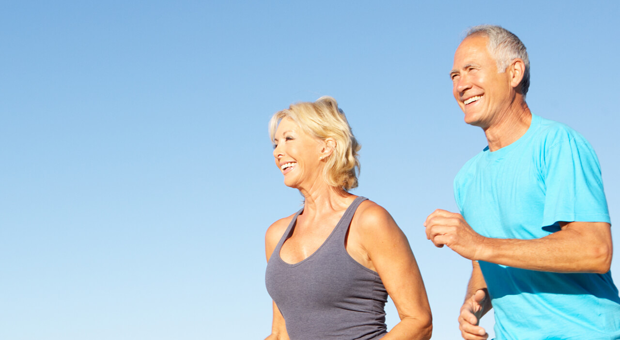 Older woman and man jogging on the beach and smiling.