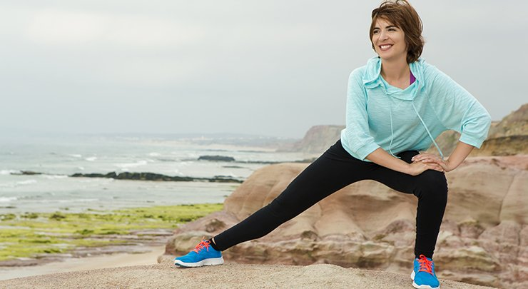 Woman smiling and stretching outside.