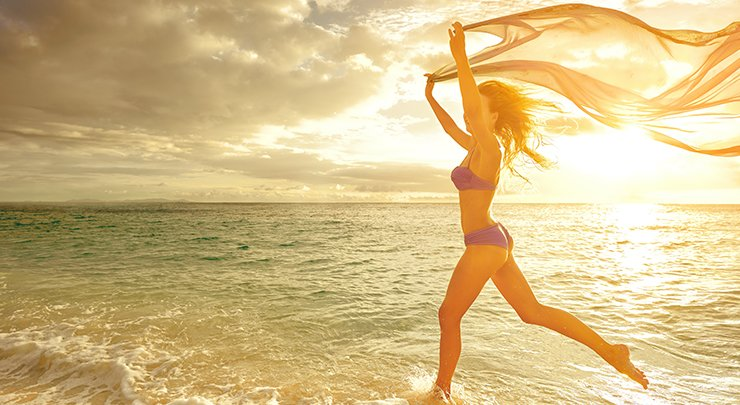 Woman wearing bikini running on beach with fabric flying through air.
