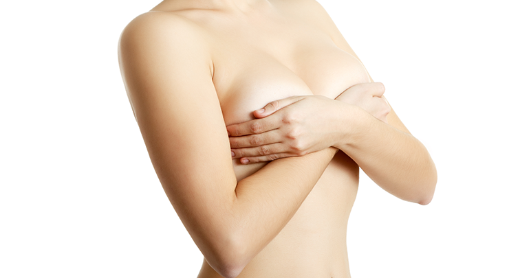 Woman covering her breasts up with crossed arms.