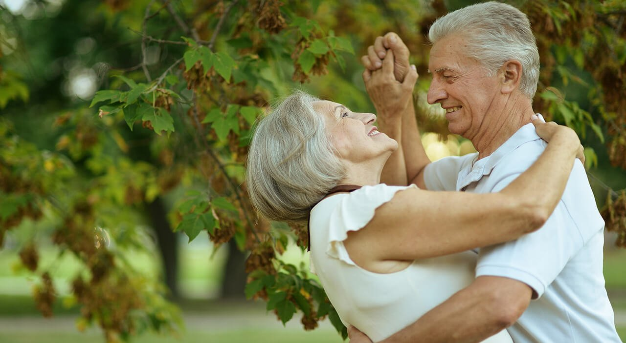 Older woman smiling up at her husband as they dance together in the park.