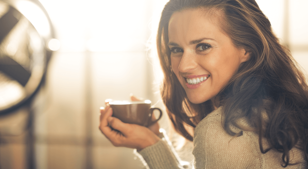 Woman wearing beige sweater and smiling as she drinks coffee.