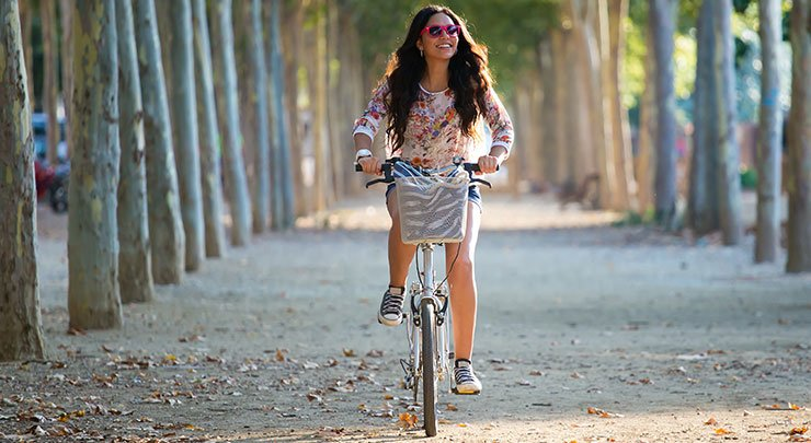 Young woman wearing pink sunglasses and riding bicycle.