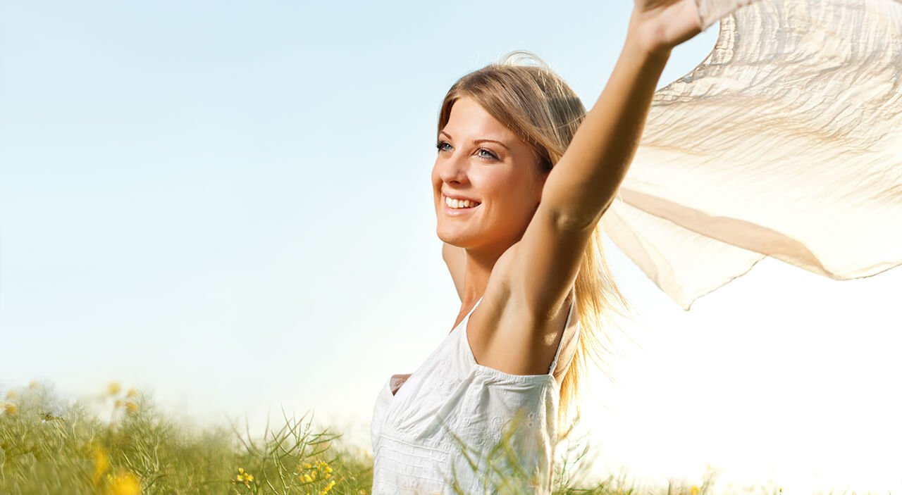 Blonde woman smiling and looking to left as she holds a silk up in the air for the wind to blow through it.