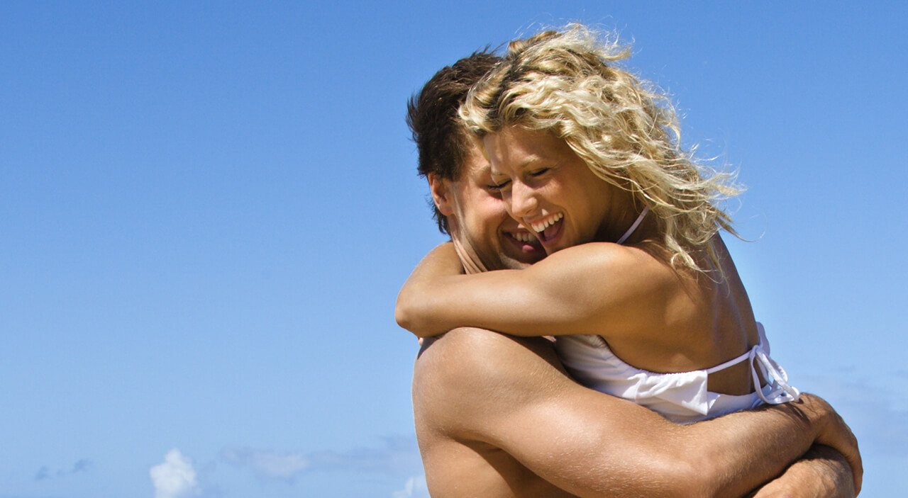 Blonde woman hugging man with brown hair while they both smile on the beach against a blue sky.