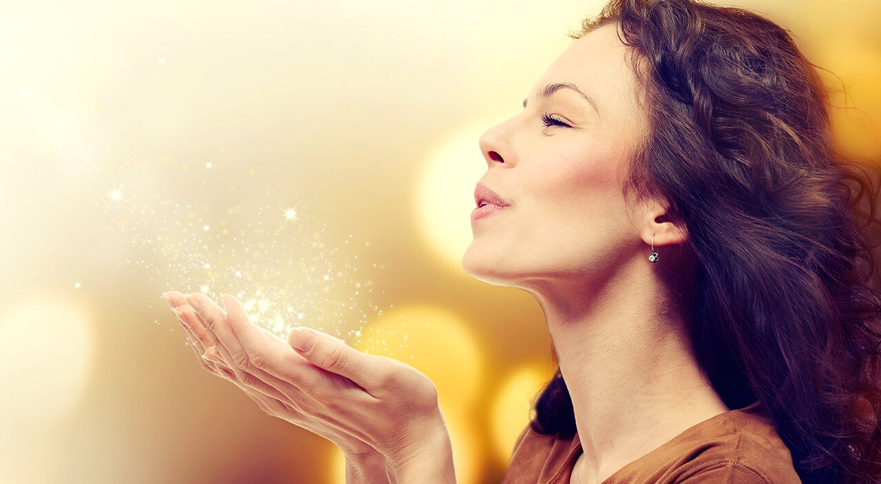 Brunette woman holding up sparkles in her hands and blowing them while smiling.