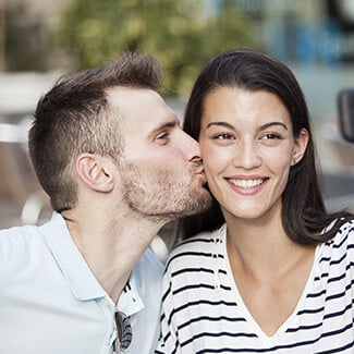 Woman with brown hair smiling as she gets kissed by her boyfriend on the cheek.