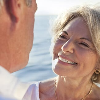Older woman with smooth skin smiling at her husband on the beach.