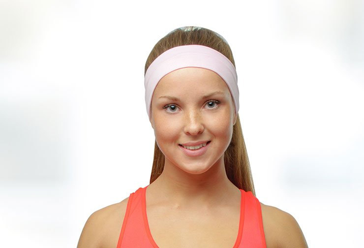 Young woman wearing pink headband after otoplasty.