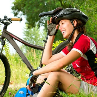 Woman wearing bike helmet and cycling clothing sitting besider her bike at the park.