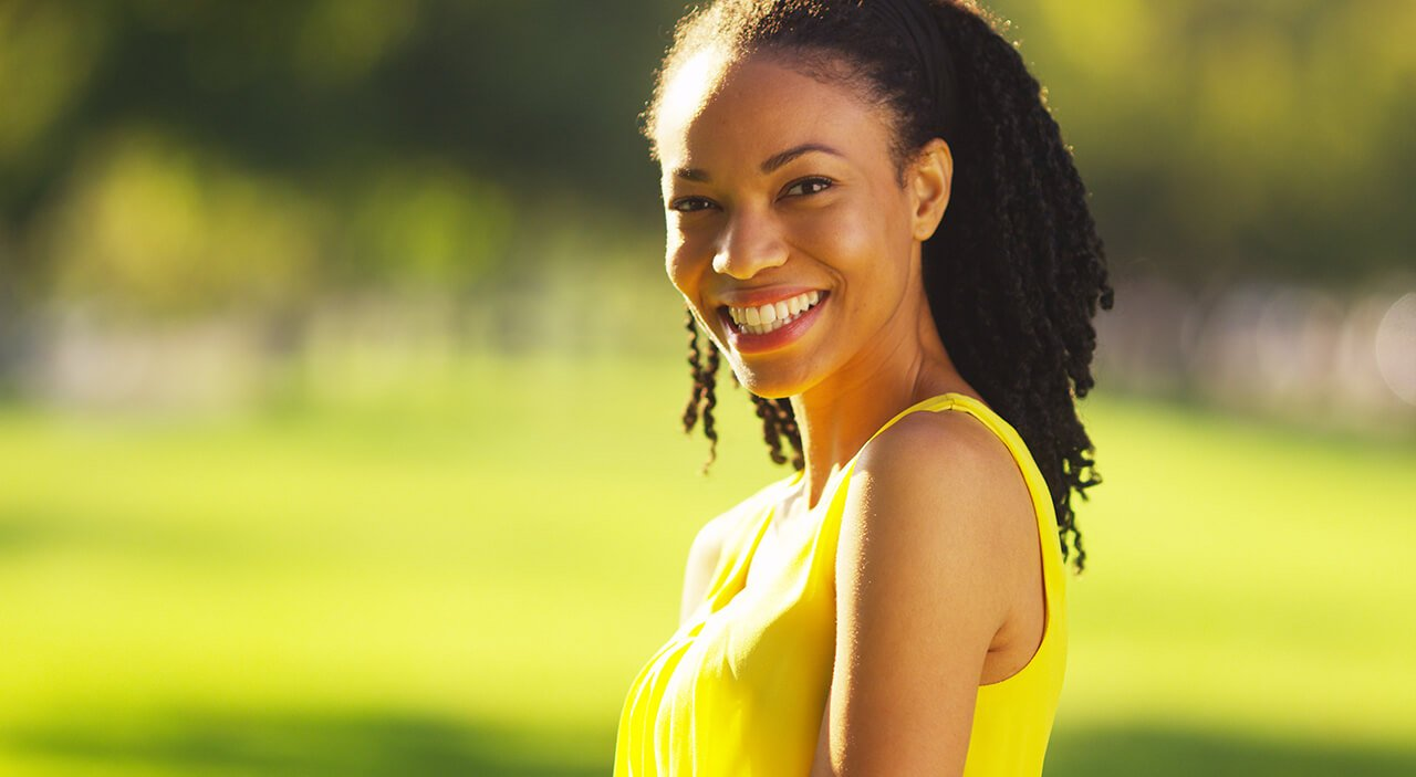 Woman wearing yellow dress smiling in park during summer.