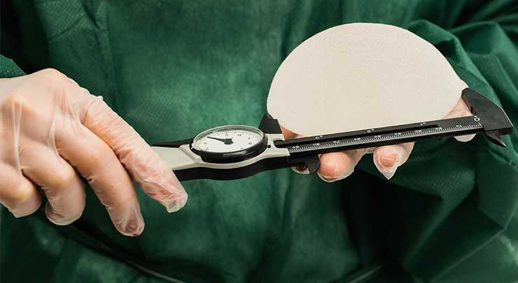 Plastic surgeon holding breast implant and ruler measuring breast implant size.