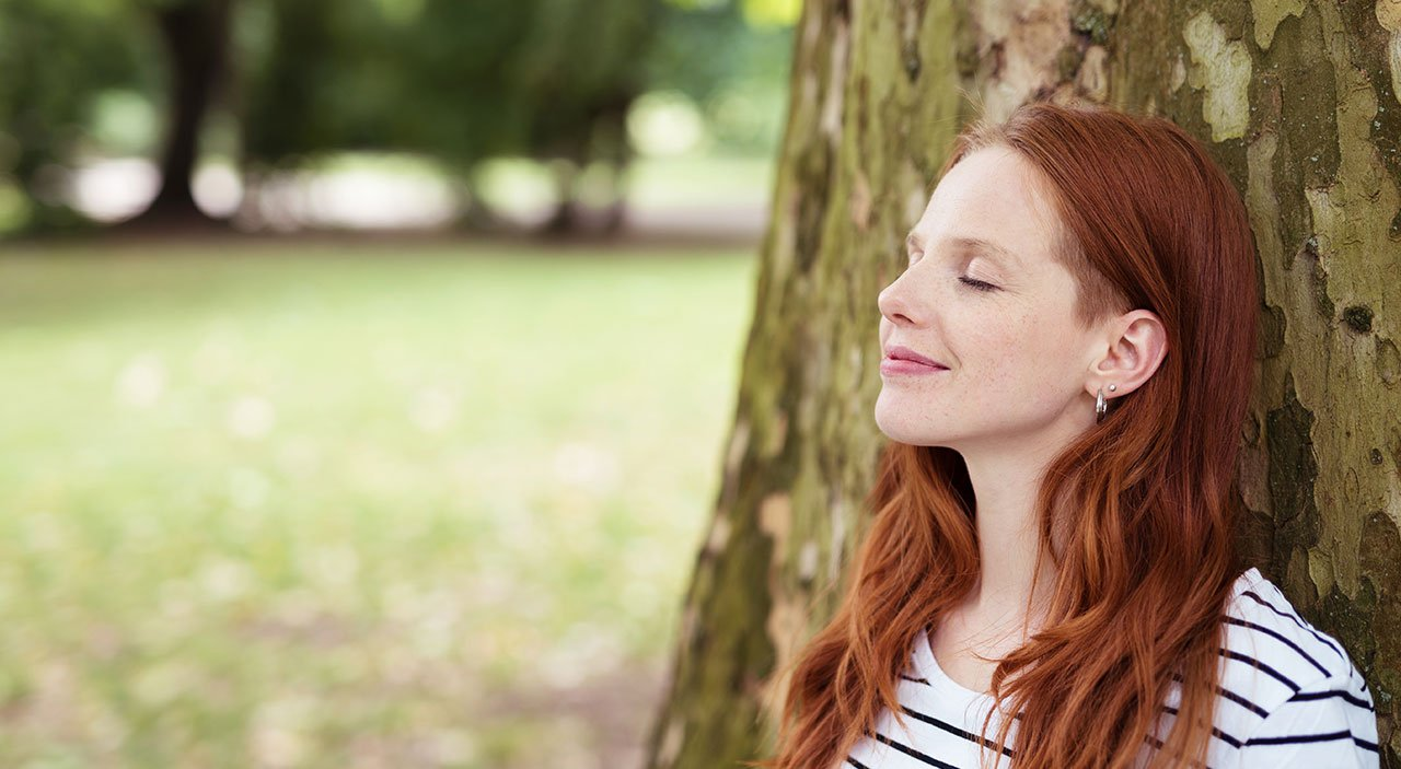Woman with eyes closed and head tilted up, smiling at the sky and leaning against a tree.