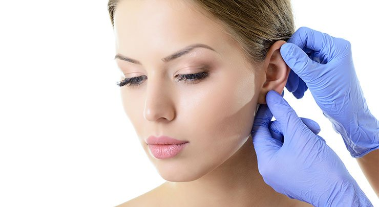 Woman having her ear inspected by a doctor wearing blue rubber gloves.