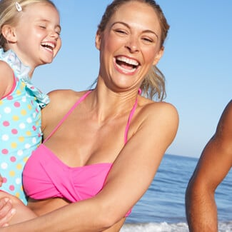 Laughing woman with daughter, husband and son at the beach.